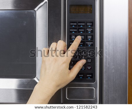 Hand preparing to activate defrost mode on microwave oven - stock photo