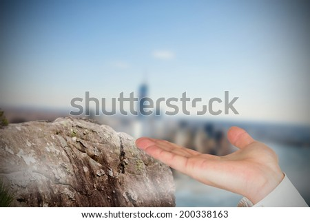Hand presenting against large rock overlooking foggy city - stock photo