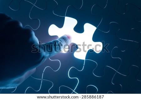 Hand press on jigsaw, conceptual image of business strategy - stock photo