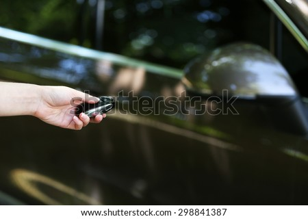Hand presses on remote control car alarm systems - stock photo