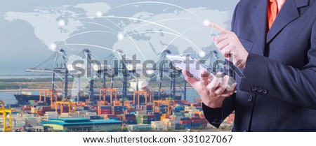 hand presses on world map with digital tablet,Industrial Container Cargo freight ship  at dusk for Logistic Import Export background (Elements of this image furnished by NASA) - stock photo