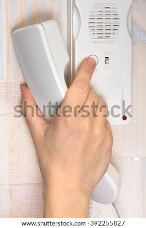 hand pressing a button on the intercom - stock photo