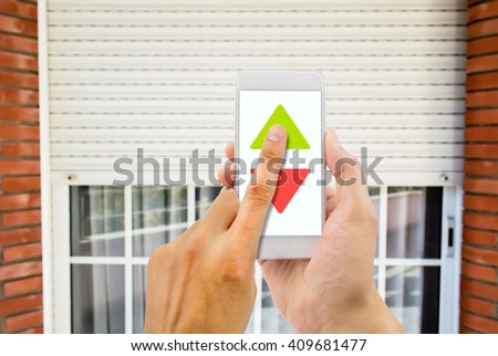 hand pressing a smartphone with remote control controlling an electric roller shutter - stock photo