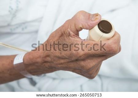 Hand pressing emergency nurse call button - stock photo