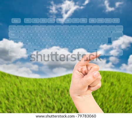 Hand pressing keyboard transparent on the blue sky field. - stock photo