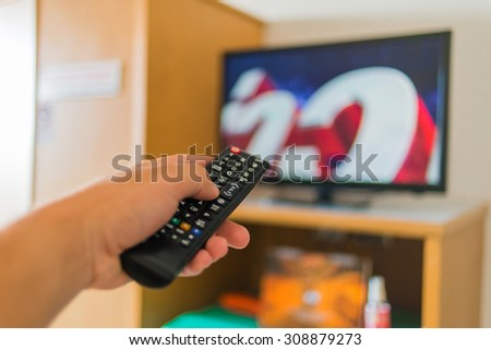 hand pressing remote control to the TV, television - stock photo