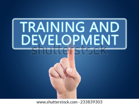 Hand pressing Training and Development button on interface with blue background. - stock photo