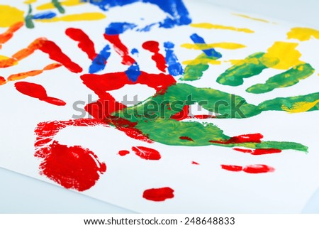 Hand prints of paint on white background - stock photo