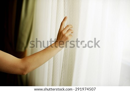 Hand pulling a window curtain for warm daylight to enter the room - stock photo