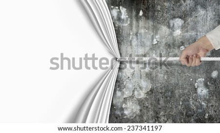 hand pulling blank curtain covered old dirty mottled concrete wall isolated on white background - stock photo