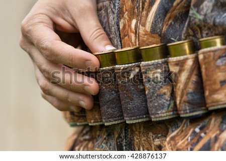 hand pulling cartridge from the bandoleer  - stock photo
