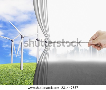 hand pulling gray cityscape curtain revealing group of wind turbines, environmental protection and alternative energy concept - stock photo