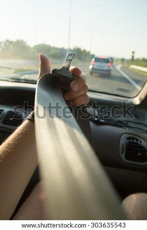 Hand pulling seat belt in the car - stock photo