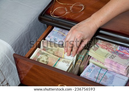 Hand pulls out banknote and wad of money from the bedside table filled with Ukrainian cash - stock photo