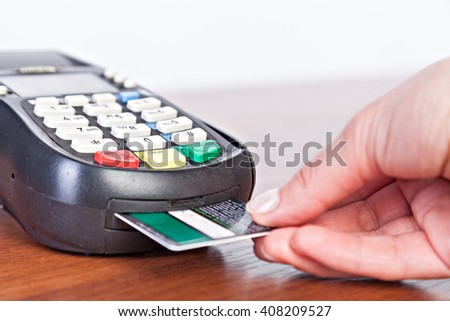 Hand push credit card Into a credit card machine.Studio shot. Selective Focus. - stock photo