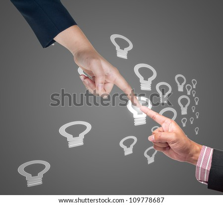 Hand pushing bulb light button on a touch screen interface - stock photo