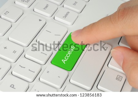 Hand pushing green access button of the keyboard - stock photo