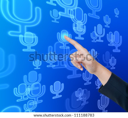 Hand pushing microphone button on a touch screen interface - stock photo