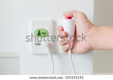 hand pushing nurse call button - stock photo