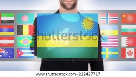 Hand pushing on a touch screen interface, choosing language or country, Rwanda - stock photo