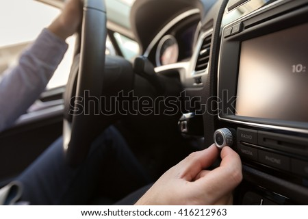 Hand Pushing the power button to turn on the car stereo system - stock photo