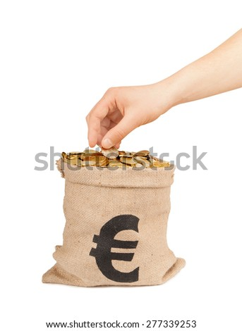 hand put coin in bag with money isolated on white - stock photo