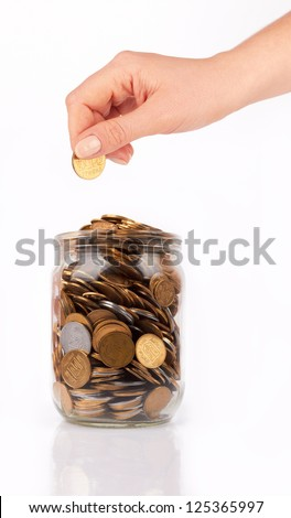 hand put coin jar with coins isolated on white - stock photo