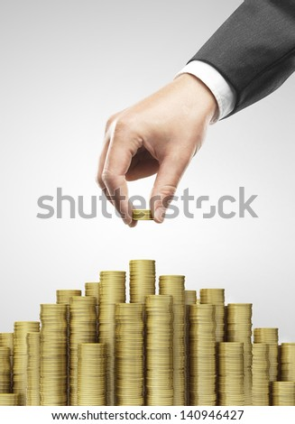 Hand put coins to money staircase - stock photo