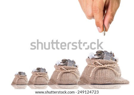 Hand put down money coin to growing bag with white background - stock photo