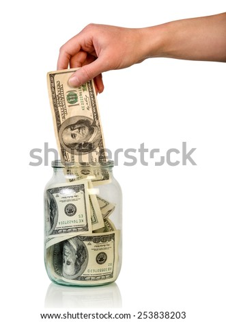 Hand puts money in jar on white background - stock photo