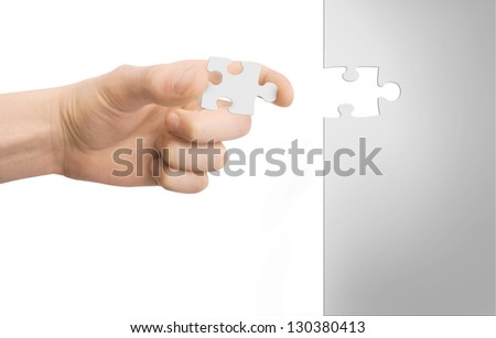 hand puts puzzle isolated on white - stock photo