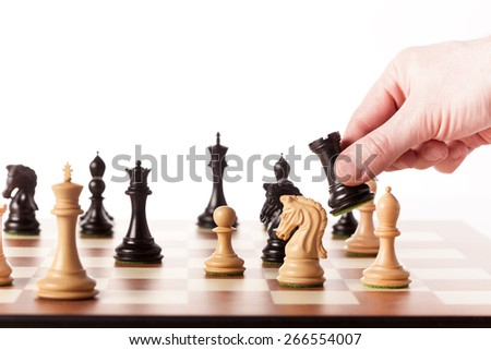 Hand putting a black chess piece on a table - stock photo