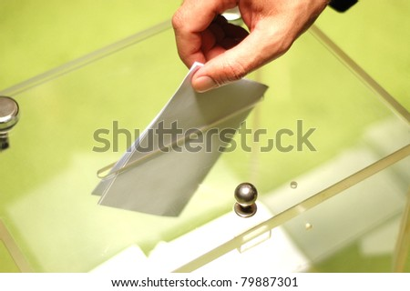 Hand putting a blank ballot inside the box, elections concept - stock photo
