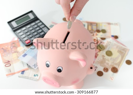 Hand putting a coin into a piggy bank - stock photo