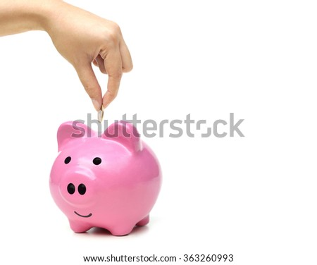 hand putting a coin into a pink piggy bank thinking of buying a new house and a car - saving money for future concept - stock photo