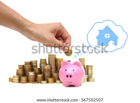 hand putting a coin into a pink piggy bank thinking of buying a new house - saving money for future concept                                - stock photo