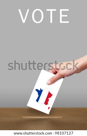 Hand putting a voting ballot to wooden box with flag of France - stock photo