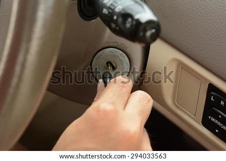 Hand putting car key on the keyhole - stock photo