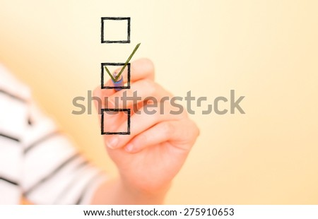 Hand putting check mark with pen - stock photo