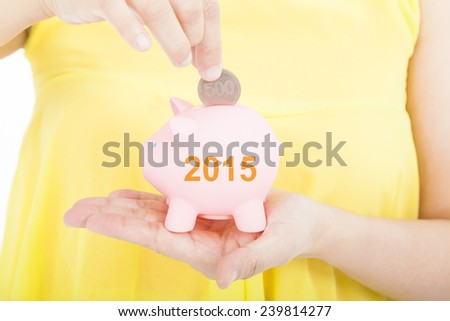 hand putting coin into a piggy bank for 2015 investment concept - stock photo