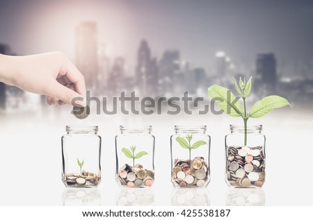 hand putting coins and seed in bottle on photo blurred cityscape background,Business investment growth concept - stock photo