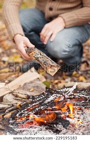 hand putting fir wood to fire - stock photo