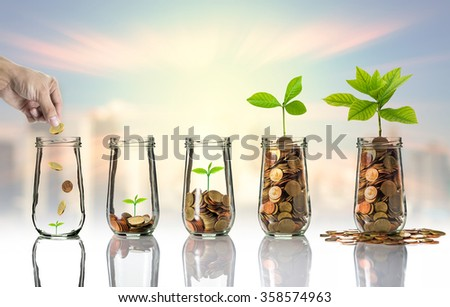Hand putting Gold coins and seed in clear bottle on cityscape photo blurred cityscape background,Business investment growth concept - stock photo