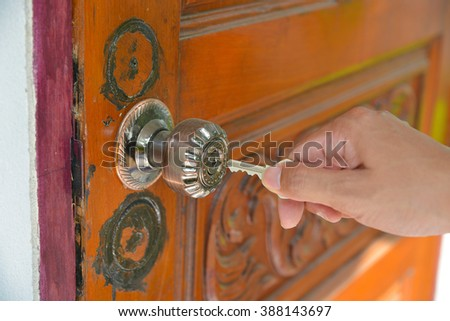 hand putting house key into front door lock of house. - stock photo