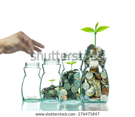 Hand putting mix coins and seed in clear bottle on white background,Business investment growth concept - stock photo