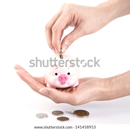 Hand putting money in a piggy bank on white background - stock photo