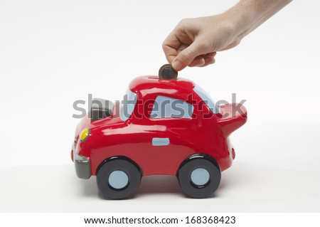 Hand Putting Money in Car Shaped Piggy Bank - stock photo