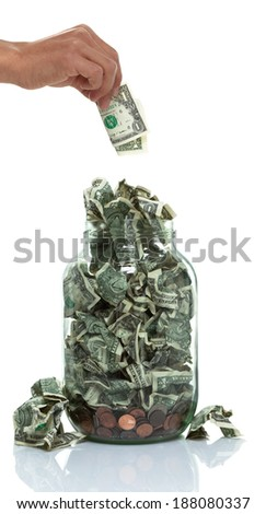 Hand putting money into a jar full of money - stock photo