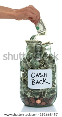 Hand putting money into a savings jar with a white cash back label - stock photo