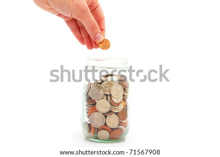 hand putting penny in a coin jar, saving money - stock photo